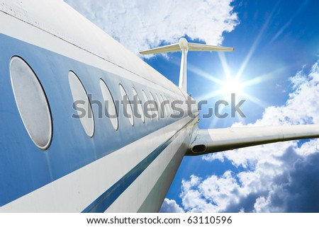 Airliner flying in high cloudy sky with bright sun - stock photo