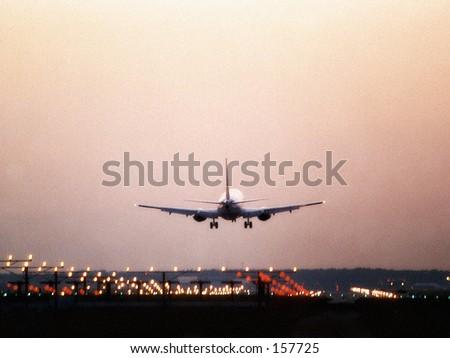 Airliner Landing in Houston at Dusk - stock photo