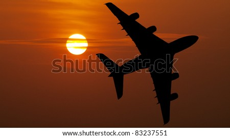 Airliner over red sunset - stock photo