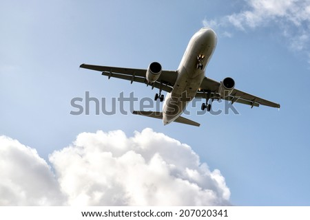 Airliner preparing for landing with a cloudy sky - stock photo
