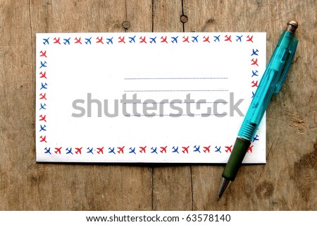 airmail and pen on wood background