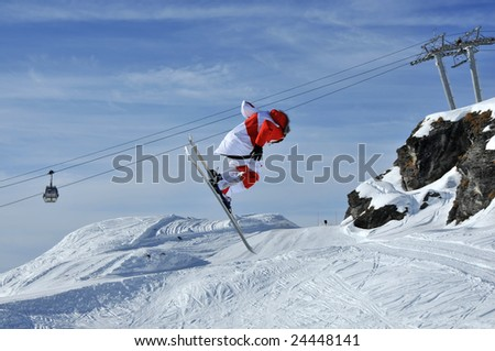 Airoski: a skier in red and white executes a full turn while airial skiing,  currently facing backwards.
