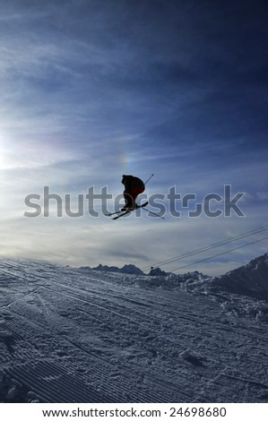 airoski: the silhouette of a skier jumping towards the setting sun