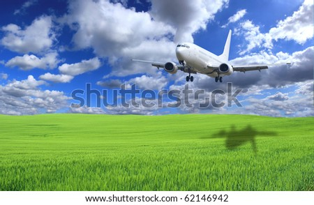 Airplane above green field - stock photo