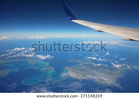 airplane above many islands and blue sea - stock photo