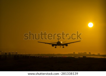 Airplane almost landed in the early morning during sunrise.