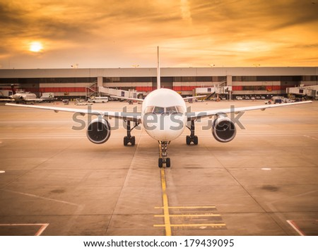 Airplane and airport scene at sunset - stock photo