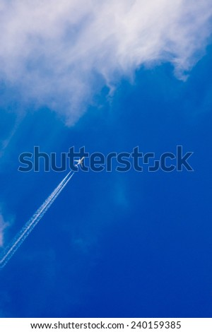 Airplane and jet trail on a blue sky heading into clouds - stock photo