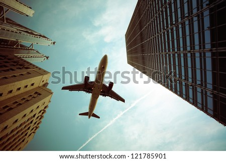 airplane and modern buildings with dramatic sky,abstract cityscape - stock photo