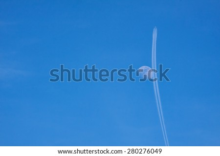 Airplane and moon in the sky - stock photo