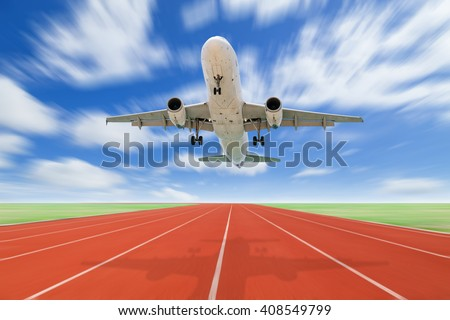 Airplane and Running track with green grass and blue sky white cloud blur background - stock photo