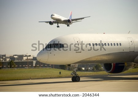 Airplane approaches as another waits to takeoff - stock photo