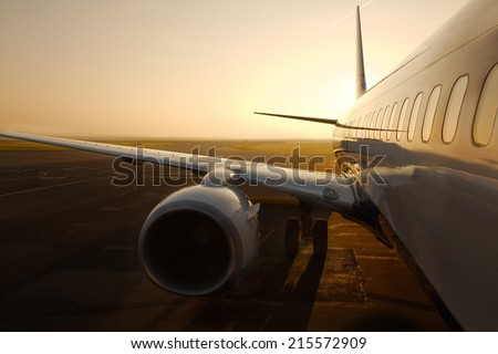 Airplane at an airport at sunrise - stock photo