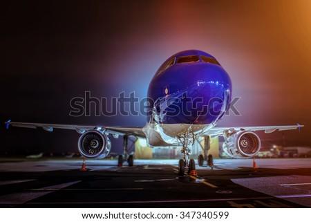 Airplane at night - back lit - stock photo