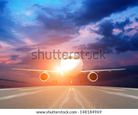 airplane at takeoff seen from the bottom in the airport landing strip at sunset - stock photo