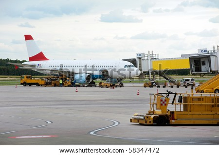 airplane at the airport being loaded with cargo - stock photo