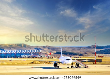 Airplane at the terminal gate  Modern international airport at sunset - stock photo