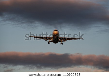 Airplane before landing in sunset - stock photo