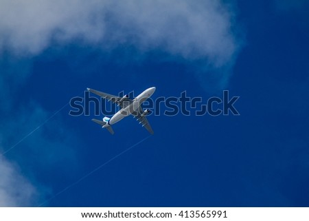 Airplane between clouds on a blue sky - stock photo