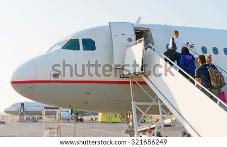 Airplane Boarding. Passengers climb the ladder. - stock photo