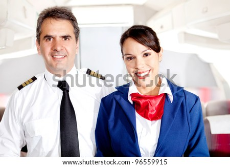 Airplane cabin crew with pilot and flight attendant smiling - stock photo