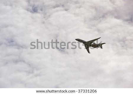 airplane climbing into a cloudy sky - stock photo