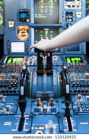 Airplane Cockpit thrust levers with hand on top for takeoff - stock photo