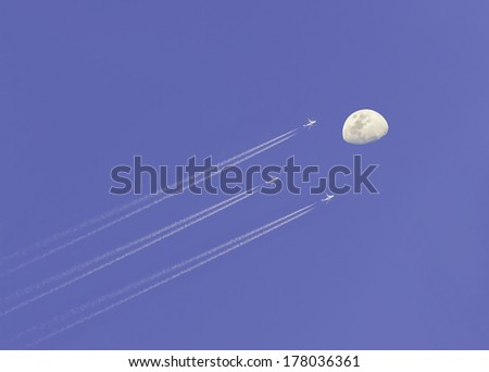 Airplane condensation line on sky with moon - stock photo