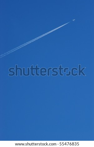 Airplane contrail against blue sky with copy space - stock photo