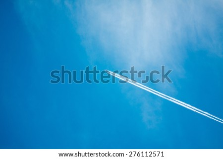 airplane contrail against clear blue sky - stock photo
