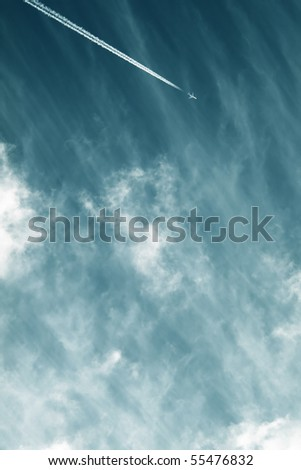 Airplane contrail against sky with diffused white clouds with copy space - stock photo