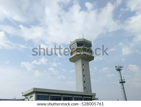 Airplane control tower with clouded sky behind
