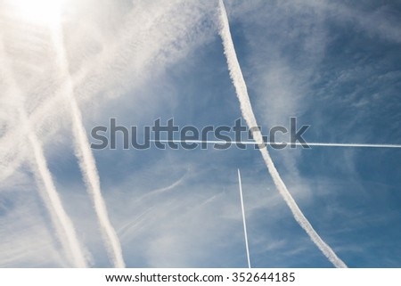 Airplane crossed condensation trails and lines in blue sky. Abstract background. - stock photo