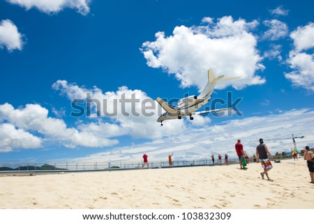 Airplane descending very low over a sandy beach as bystanders look on in amazement.