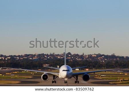 airplane drives in driveway in airport on land under blue clear sky - stock photo