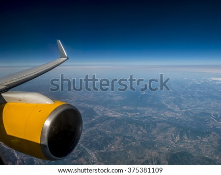 airplane engine and wing high up in the sky