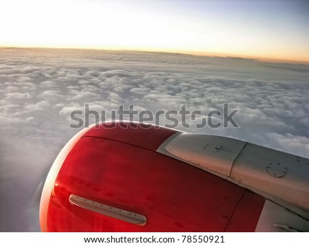 Airplane engine during a fly in sunset sky - stock photo