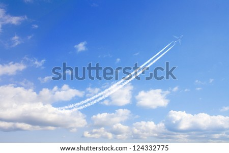airplane flies in white clouds in a blue sky and leaving trail - stock photo