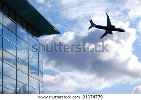 Airplane flies over glass window office building