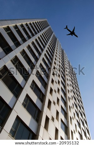 Airplane flies over tower block prior to landing