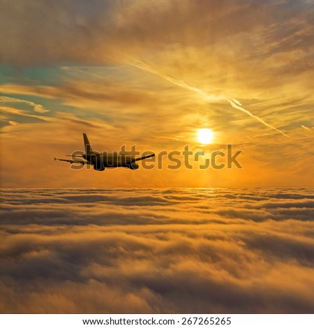 Airplane flight above stratum of clouds against golden bright sunset sky - air traffic concept or background