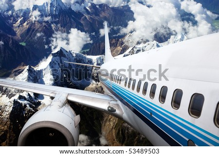 airplane fly above the mountain with clouds. - stock photo
