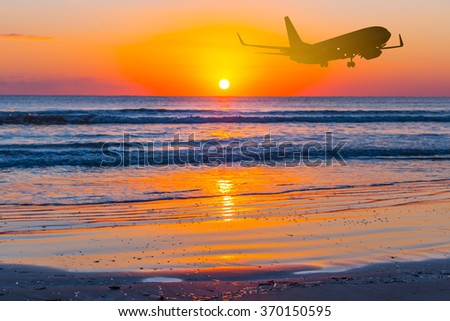 airplane fly over a sea beach at the sunset - stock photo