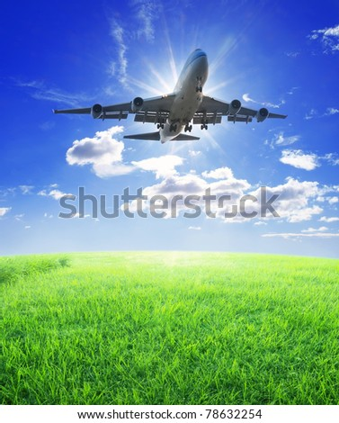 Airplane fly over grass - stock photo