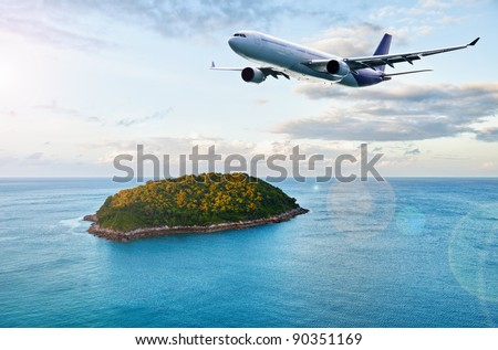 Airplane flying above ocean with beautiful small island. - stock photo