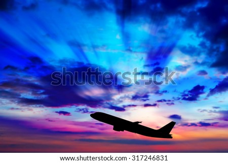 Airplane flying at sunset - stock photo