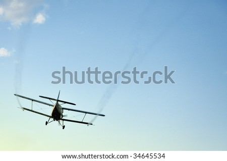 Airplane flying away in a clear, blue summer sky.