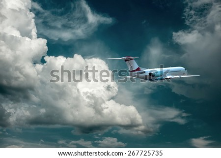 Airplane flying in the sky with clouds - stock photo