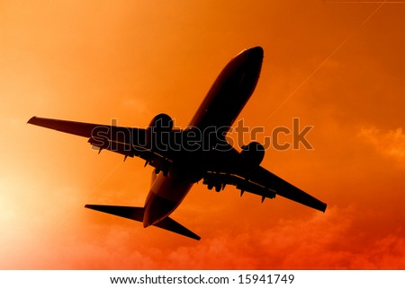 airplane flying in the sunset - stock photo