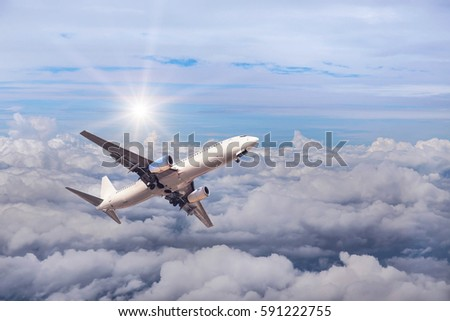 airplane flying in to sky high altitude above the white clouds with sunlight